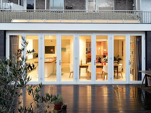 via Bloem en Lemstra Architecten. Dining space with a LOT of natural light through big wall doors. View from outside deck.