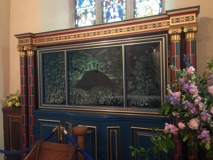 The beautiful Engraved Glass Triptych by Simon Whistler, designed by his father Sir Laurence Whistler, in Salcombe Regis Church near Sidmouth, Devon. The centre panel depicts the Crucifixion with Salcombe Regis Church below