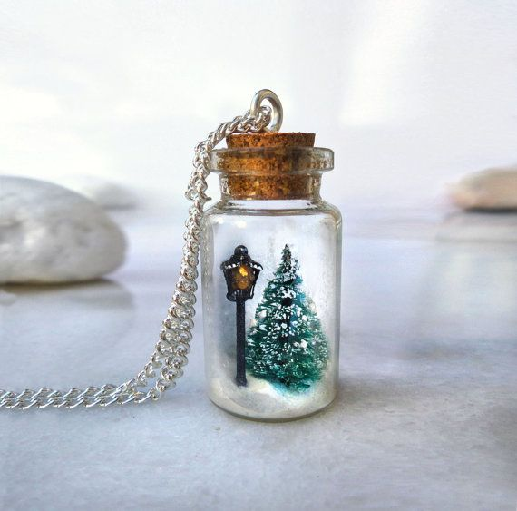 This snow globe bottle necklace features a scene from The Chronicles of Narnia - a street lamp in the middle of a snowy forest. The little scene is