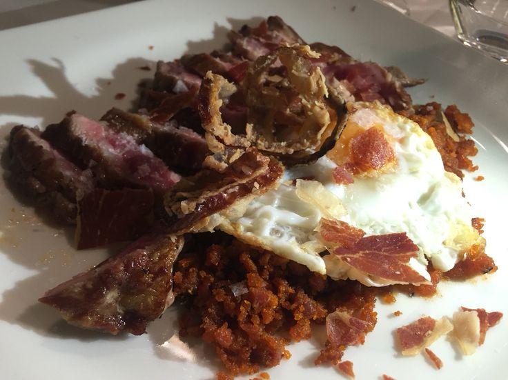 Pluma de cerdo con migas de jamón ibérico y huevo frito.