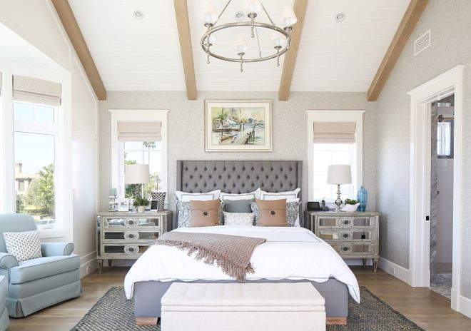 Bedroom. This master bedroom features textured gray wallpaper, vaulted ceilings with exposed beams, light color wood floor and an elegant tufted headboard flanked by mirrored night stands. #bedroom Patterson Custom Homes. Interiors by Trish Steele, Churchill Design.