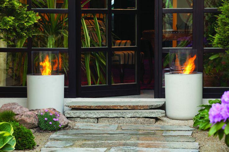 Jar Commerce. Szklany cylinder osadzony jest na betonowej podstawie o średnicy 41 cm. Wysokość modelu – 75cm. Biokominek Jar Commerce jest idealnym rozwiązaniem na wprowadzenie ognia na taras czy do strefy relaksu w spa. Ciepło ognia zestawione z zimnem betonu to pomysł znanego francuskiego projektanta, Christopha Pillet.