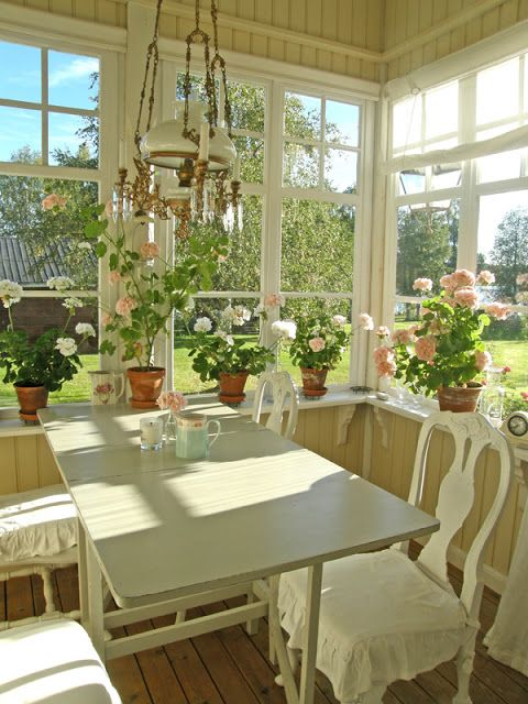 Inside a traditional Swedish glassed porch at summertime with lots of geraniums