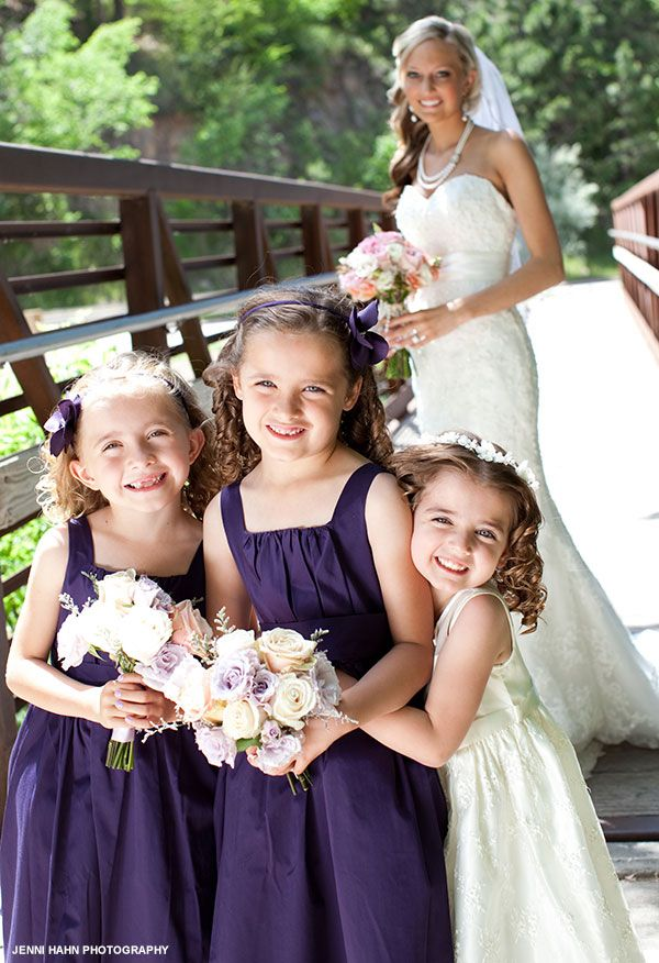 Two junior bridesmaids in purple and the flower girl in white pose in front of the bride