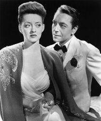 "Bette Davis and Paul Henreid in ""Now, Voyager""1942 Warner Bros.** B.D.M. Black and White, Bow Tie, Evening Dress, Updo, Butterfly, Beaded Shawl, Shawl, Suit, Rose, Lapel, Looking To Side mptv_2017_Jan_to_April_Update"