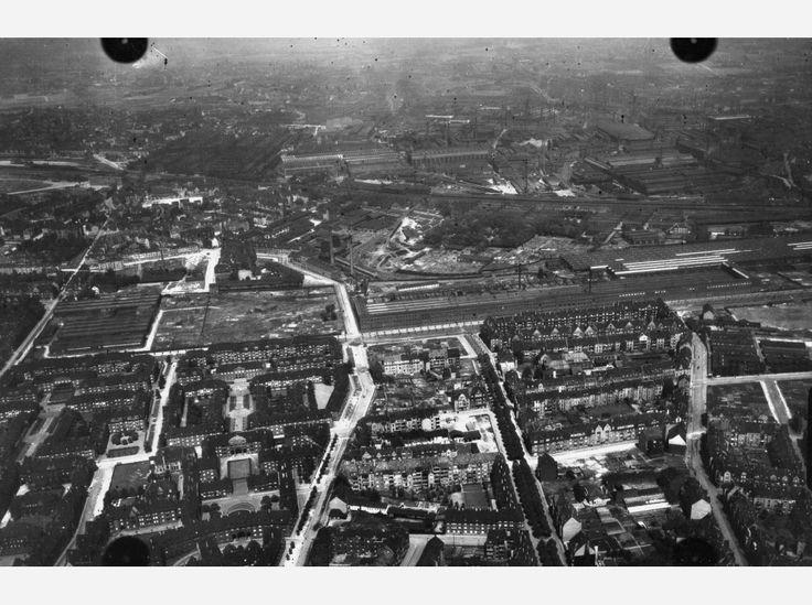 Hier: Flug 11, Bild 258. Position der Kamera: fotografiert über dem heutigen Essen-Holsterhausen, etwa über dem Bereich zwischen A40, Holsterhauser Straße, Rubensstraße/Hobeisenstraße. Im Bildhintergrund ist die Krupp Gussstahlfabrik zu erkennen. In der linken Bildhälfte (unten) ist die damalige Bebauung rund um den heutigen Thielen- und Hartmannplatz zu erkennen. Bei der Straße mit der dichten Baumbepflanzung im Stil einer Allee (Bildmitte, unten) handelt es sich wohl um die heutige…