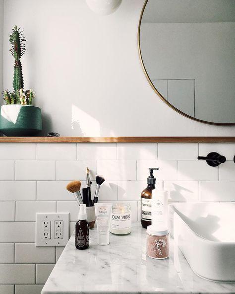 Bancada em Mármore, torneira na cor preta e o espelho redondo dão estilo ao banheiro