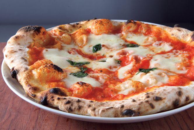 ピッツェリア「ダ・マウ」。カウンター8席、奥にテーブル8席。料理はオーナーシェフの横山さんが一人で作る。カウンター席の前にある窯でピッツァを焼き、サラダやパスタだって作る。