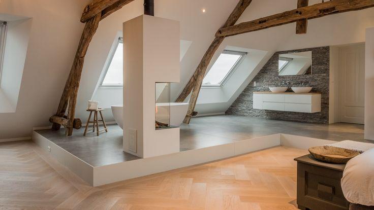 De verhoogde vloer loopt achter de gashaard tot net voorbij de oude houten spanten.