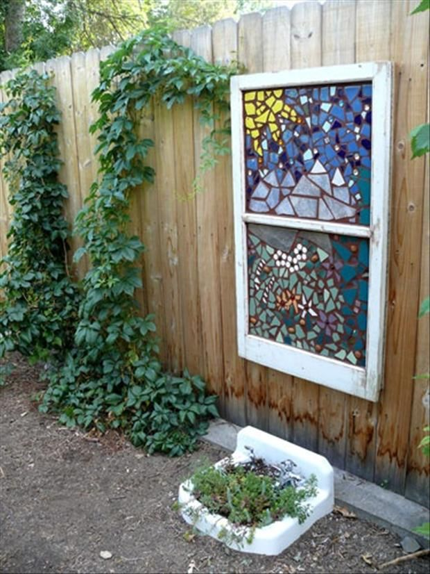 "An old window with stained glass mosaic art applied...in your garden. Check out the sink ""planter"" too!"
