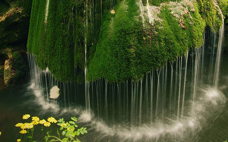 Dramatic moss covered waterfall in Romania