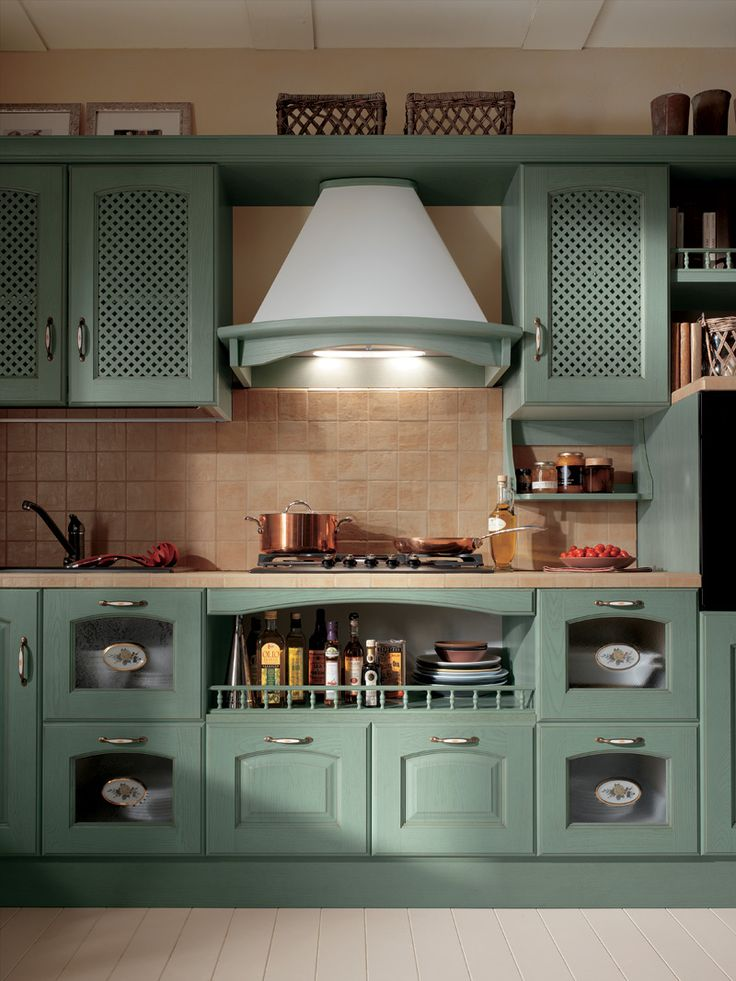 Personalized color, handles, worktops and alternative furnishing solutions come together in this composition with Green Ash doors, which includes wall units with open-fronted sections and low cupboards.