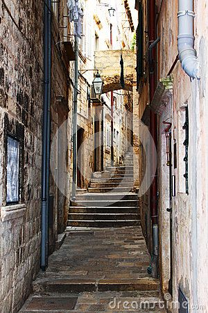 Dark old stairs on narrow pathway with stone buildings in Dubrovnik, Croatia.