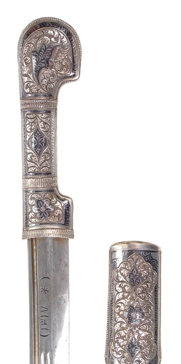 A CAUCASIAN PRESENTATION SHASHKA SWORD Mounted entirely in silver, elaborately engraved and nielloed overall in Kubachi style, the robust, multifullered blade with clipped tip struck at the left forte with crescent moons and a star and dated 1317 (1899.c.e.)