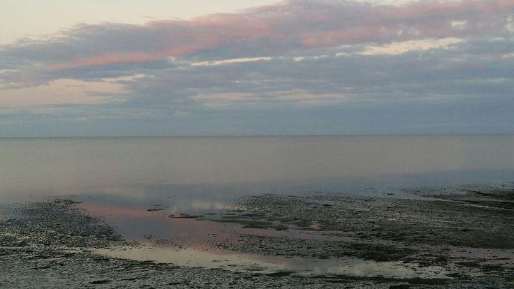 Waddenzee bij Oost op Texel. Weerkaatsing van de roze lucht in het water.