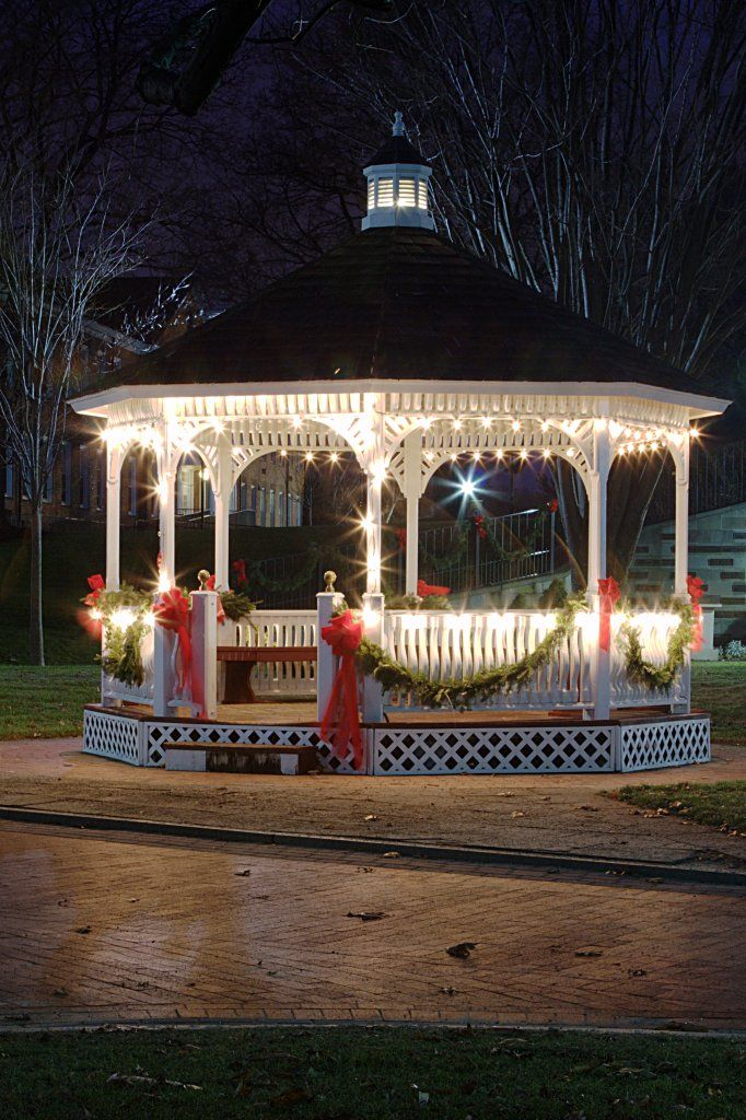 Stunning gazebo lit with fairy lights and decorated with red ribbons and garlands. Gorgeous for Christmas time! Photographed by Peter Szaben.