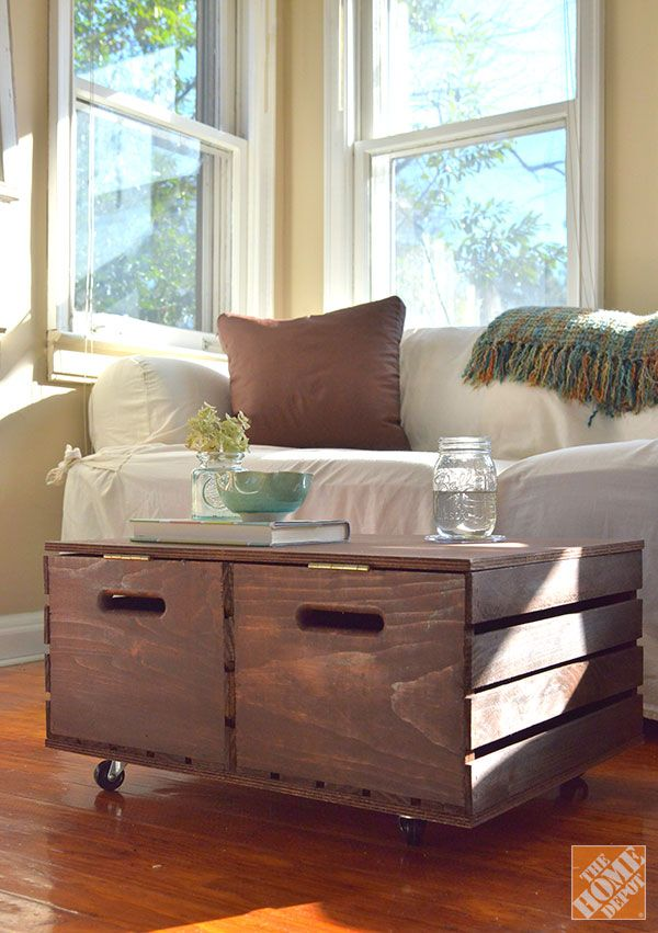 DIY Alert! This storage coffee table is made from a couple wooden crates, some plywood and casters. Click through for instructions on how to make your own!
