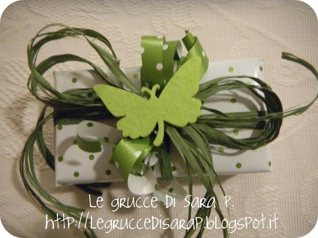 Pacco regalo con carta a pois verdi su sfondo bianco, nastro di rafia verde e farfallina in pannolenci