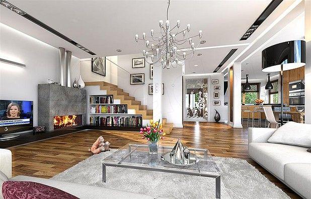 Widok z salonu na hol, fragment kuchni. Nas zachwyca duży kominek i ciekawa aranżacja schodów - sprytnie wykorzystana przestrzeń służy jako biblioteczka.