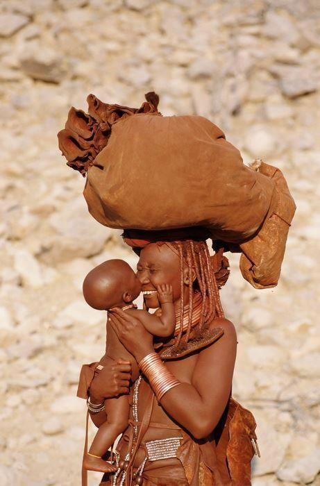 """Tribo Himba vive na região do kunene, noroeste da Namíbia. São uma tribo semi-nômade. Há quase 5 seculos, atravessaram a fronteira da Angola e se assentaram em Kaokoland (atual região Kunene). A cor avermelhada é marcante característica desta tribo, se dá pela """"Otjize"""", pasta de manteiga, gordura e ocre (as vezes perfumado com resina aromatica), que as mulheres passam duas vezes ao dia nas tranças e no corpo. Simboliza a União da cor vermelha da terra e do sangue que denota vida."""