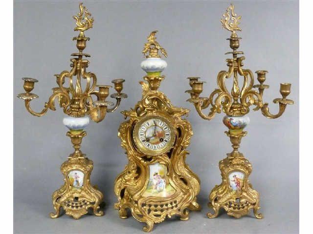 Garniture de cheminée d'époque Napoléon III en bronze doré de style rocaille et éléments en porcelaine peinte, comprenant une pendule. Haut. : 55 cm et une paire de candélabres à cinq lumières. Haut. : 63 cm