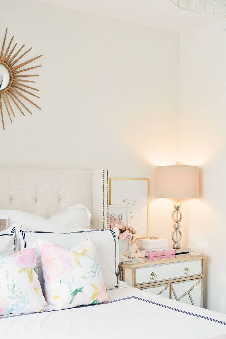 Create a relaxing space to drift off in by using pale throws, soft lighting, + a blush accent.