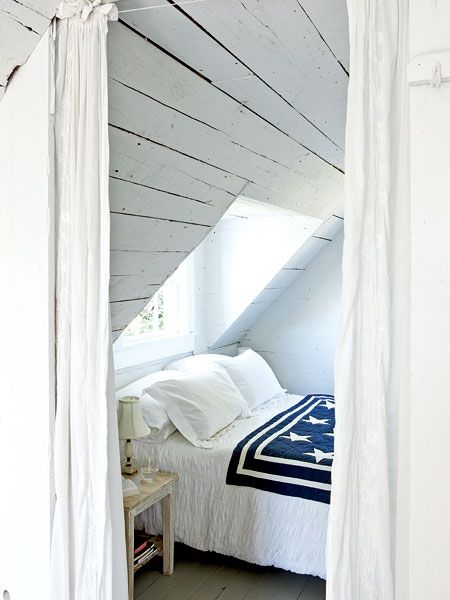Nautical Master Bedroom ~ With vaulted ceilings and whitewashed wood paneling, this master bedroom is made only for sleeping. A simple blue-and-white quilt enforces the nautical island look of this coastal Maine sleeping space.