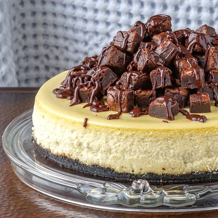 Brownie Cheesecake. A luscious, creamy vanilla cheesecake sits atop a chocolate cookie crumb crust, topped with mounds of mini brownies and a drizzle of rich chocolate ganache.