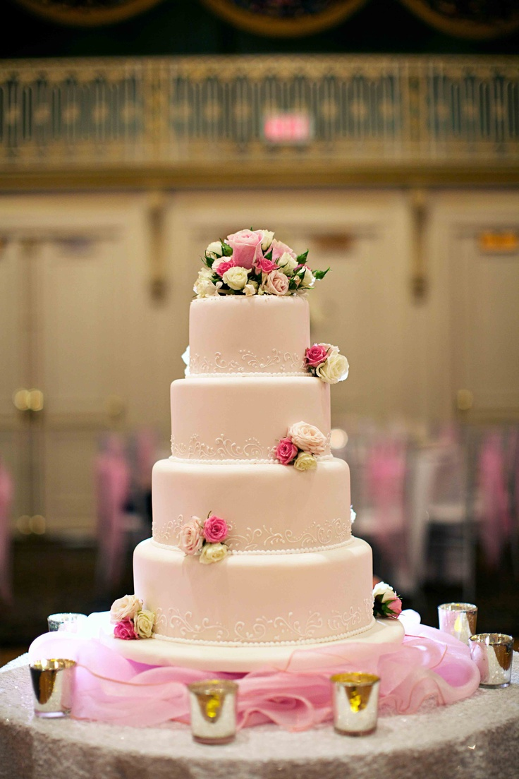 Wedding cake designed by the staff at the Fairmont Palliser Hotel in Calgary, Alberta. Icing was the palest of pinks with lace detailing at the base of each of the tiers; flower boutonnieres with pink and cream colored spray roses were used as ornamentation. Photo by Andras Schram Photography