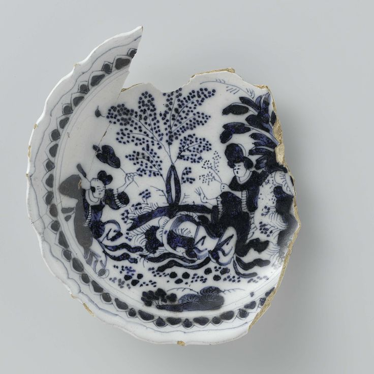 Anonymous | Schotel (fragment) met geschulpte rand en blauw beschilderd met Chinezen ter weerszijden van een boom, Anonymous, c. 1650 - c. 1690 | Schotel (fragmentarisch) van blauw beschilderde faience, met een geschulpte rand. Op de schotel zijn figuren (Chinezen) aan weerszijden van een boom geschilderd. De schotel is een bodemvondst uit Delft.