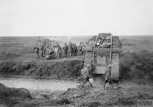 © IWM (Q 6337) A tank of 'G' Battalion, Tank Corps, 40th Division, passing captured German field guns at Graincourt on its way to take part in the attack on Bourlon Wood, 23 November 1917.