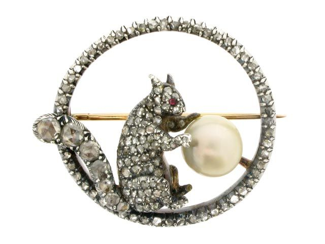 Antique pearl and diamond squirrel brooch, circa 1870. A gold and silver brooch in the form of an open circle composed of a single row of round rose cut diamonds in silver cut down settings, and centred with seated silver squirrel pavé set with round rose cut diamonds, all one hundred thirty one diamonds with an approximate total weight of 2.00 carats, the squirrel also with a cabochon ruby eye and holding a spherical pearl, the reverse in gold and mounted with a hinged gold pin with open…