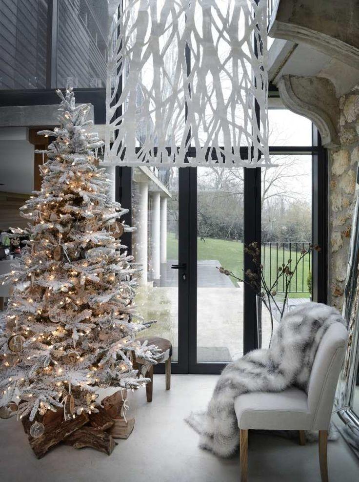 sapin de Noël artificiel en blanc décoré de guirlandes lumineuses dans le salon scandinave