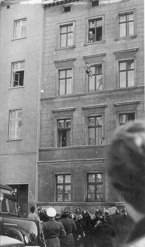 People would jump out of buildings to reach west Berlin. (Notice the firemen catching below) Later all of these buildings were torn down by the East Berlin goverment and replaced with an empty no-mans' land with landmines and guard towers to shoot people who tried to cross.  Passer le mur de Berlin à tout prix.