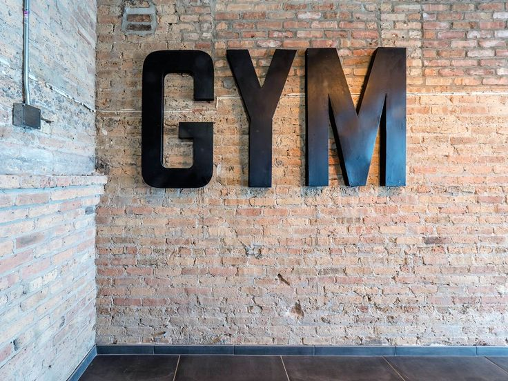 The fitness center at these boutique loft apartments in the Streeterville neighborhood of Chicago has boxing and TRX weight training equipment with an exposed brick back drop | Domu Chicago Apartments