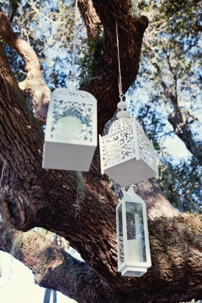 White Moroccan Lanterns hanging from the trees