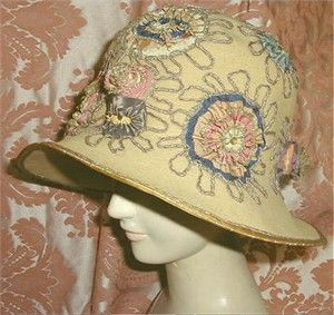 920s GAGE Ribbon & Gilt Cloche  Luscious gilt metallic and silk ribbon work adorn this beautiful 1920's cloche.   Supple fine wool felt in a pretty ochre tan color, this deep cloche was made by famed millinery house of Gage (Chicago, New York and Paris) and was based on a Paris couture design.  The ribbon work is all expertly hand done and is lush and oh so pretty with scallops, frills, star flowers, and plump silk buds, all edged in gold metallic edges.  The brim is wired to keep its shape…