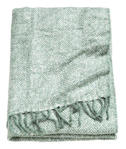 H&M  En dimgrön, jacquardvävd pläd i mjuk bouclékvalitet med fiskbensmönster. Pläden har fransar på kortsidorna. 130x170 cm. 100% akryl. Maskintvätt 30˚.  399 SEK