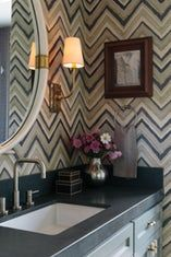 Chevron patterned wallpaper in a moody powder room
