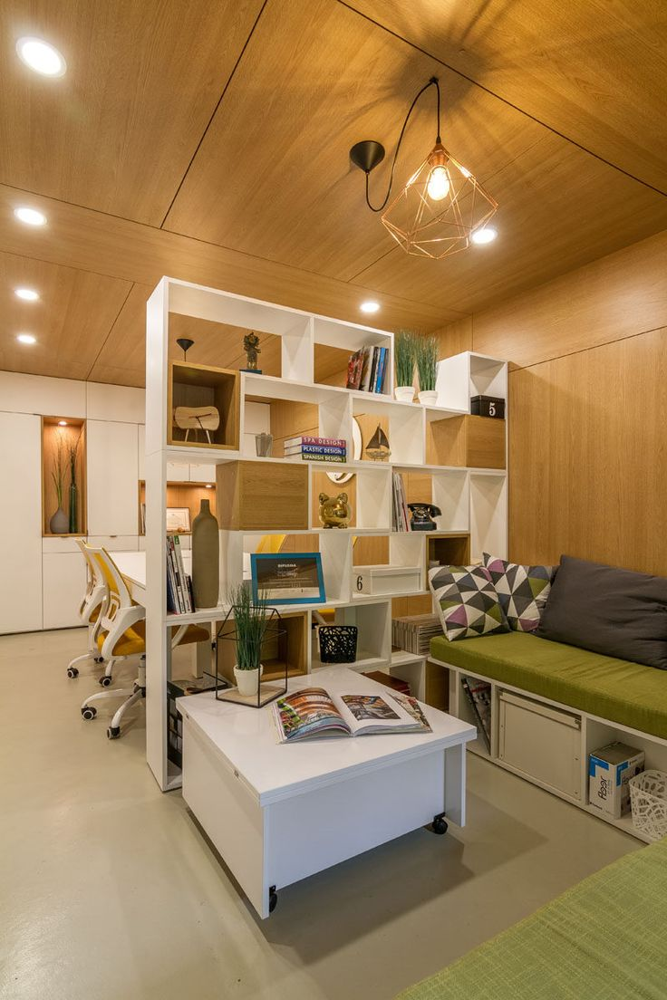 A double-sided bookshelf has been used as a room divider, with some sections blocked off with wooden boxes, providing cubby holes for decorative items.