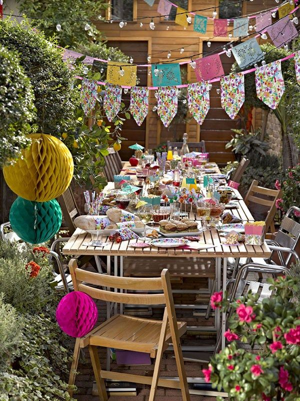 Talking Tables Fiest Summer Party paper banners!! A glorious way to decorate your garden for a summer barbeque. You could use printable banners or buy some. The hanging paper lanterns and party lights are fabulous!