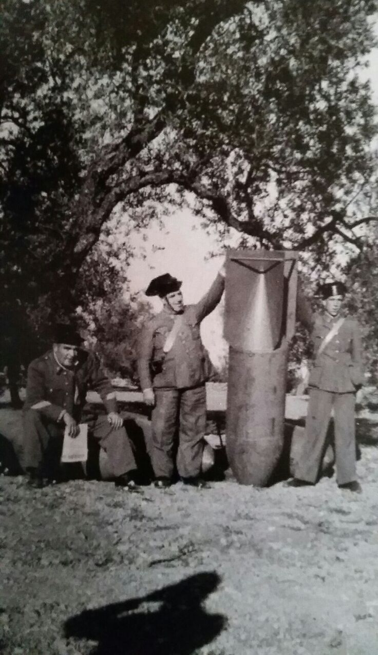 Three policemen (Guardia Civil Española) pose next to a SC500 bomb, somewhere in…