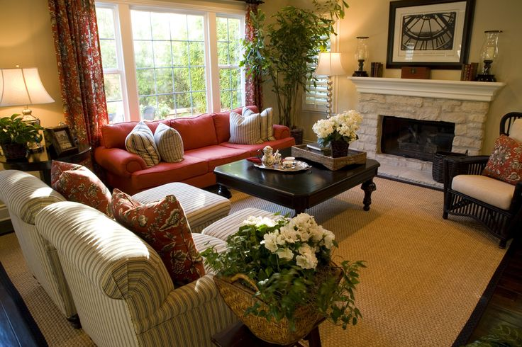 Bright red punctuates this room lit by large windows, featuring dark wood floor with tan rug, plus black reading chair and ottoman.