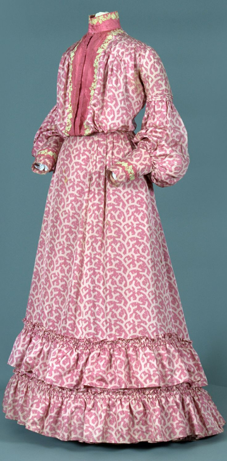 Day dress ca. 1900s. Three pieces: bodice, skirt, boned collar. Pink & cream print treated silk, pink silk front facing, cotton muslin ruffle at hem, cotton lace floral appliqué, grosgrain synthetic ribbon as waist tape. Fitted silhouette, no boning, pleating at front that adds volume, bishop sleeves gathered in at tier, pintucks down back. Floral lace appliqué at bodice front & cuffs. Full skirt, longer in back, double layer of ruffles & ruching. Vassar College