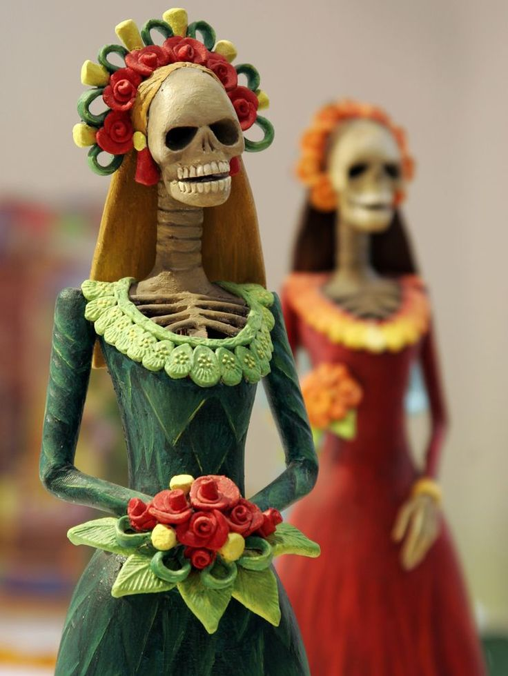 Calacas and calaveras are everywhere on Dia de los Muertos: masks, makeup, posters, and decorative figurines like these catrinas.