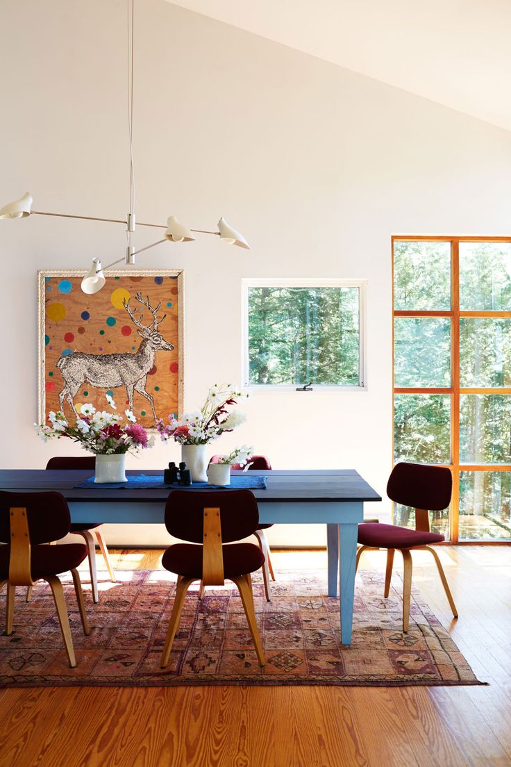 Vintage Thonet chairs (in a lesser-known style), recovered in Knoll fabric, surround a Shaker-style dining table built by Moore......Bring in a Hit of Modern Above the table, the Cross Cable light fixture by David Weeks adds contemporary edge to the rural scene, while echoing the shape of the stag horns in the painting by Jared DeFrancesco.