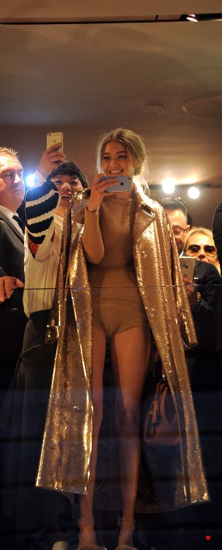 Gigi Hadid in long, gold sequined jacket and tan romper with messy bun hairstyle