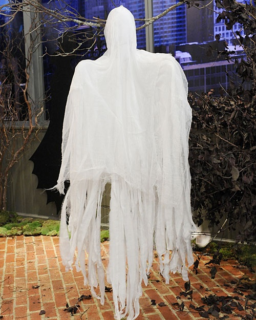 "Cheesecloth Ghosts Outdoor Halloween Deco:   James ""Figgy"" Noonan makes spook-tacular ghost decorations out of cheesecloth. Hang these easy-to-make cheesecloth ghosts from tree branches and porch railings to create a haunting Halloween scene. Tools and Materials:   Two white wire hangers,   Scissors,   One pair of white pantyhose,   Polyester stuffing,   Pliers,   16-gauge wire,   Wire cutter,   Gauze fabric, muslin, cotton sheets, or any lightweight fabric,   Safety pins,   2 yards cheesecloth,   Brewed cold coffee in a spray bottle (optional)  Cheesecloth Ghosts How-To:   1. Straighten two wire hangers into two long loops, leaving hooks intact. Twist the hooks together to form a base for the neck, then twist and form loops into arms. 2. Cut the legs from a pair of white pantyhose. Stuff each leg with polyester stuffing and slide one leg onto each wire arm. Tie legs together around wire neck.  3. Stuff waist of pantyhose to create head, and place on wire neck. Tie excess material around wires to secure. Using pliers, bend tips of wire and attach 16-gauge wire to create hook.   4. Cut a 3-yard piece of gauze or lightweight fabric lengthwise down the middle. Snip into the short edges of the fabric at an angle every 2 inches. Drape the pieces over each arm, pinning at neck to secure. 5. Cut a 2-yard piece of cheesecloth down the middle. Poke wire hook through center of both pieces of fabric, draping over head and arms. 6. Spray entire ghost or just the bottom few inches with coffee, if desired, before hanging."