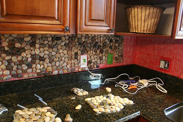 Stone backsplash idea for kitchen...This is a very neat idea. Also budget friendly : ) I think it would be cool to stencil out any shape of your kitchen theme like a coffee mug or saying and fill it in using these stones.