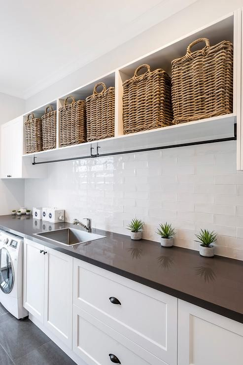 A black drying rack is mounted under laundry room shelves filled with wicker baskets.